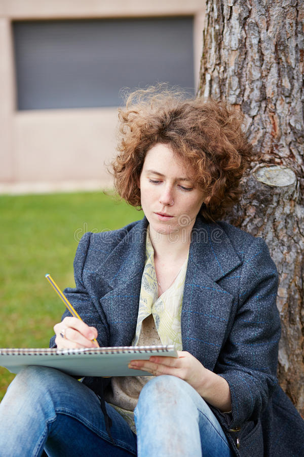 Étudiant en art roux féminin dessinant dehors image stock