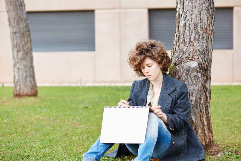 Étudiant en art roux féminin dessinant dehors photographie stock