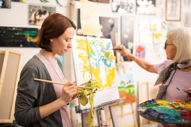 Étudiant en art séchant son pinceau après gouache verte photo stock