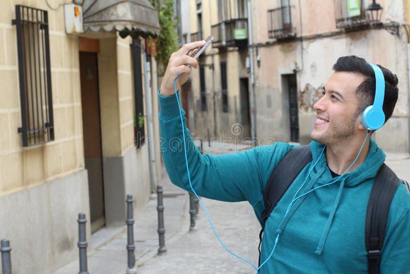 Étudiant ethnique à la mode se dirigeant à l'université prenant un selfie avec son smartphone image stock
