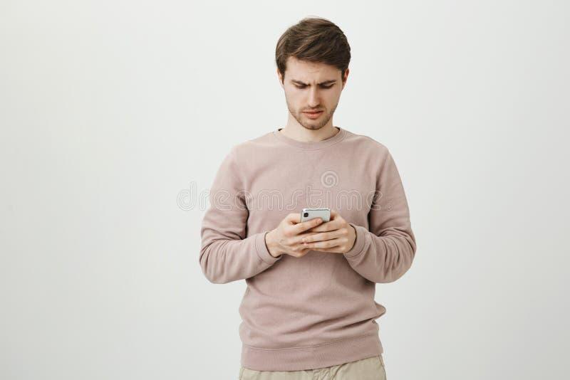 Étudiant européen bel sombre mécontent regardant le smartphone tout en passant en revue ou textotant et étant déçu photos stock