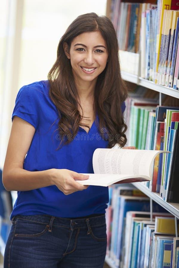 Étudiant féminin étudiant dans la bibliothèque images stock