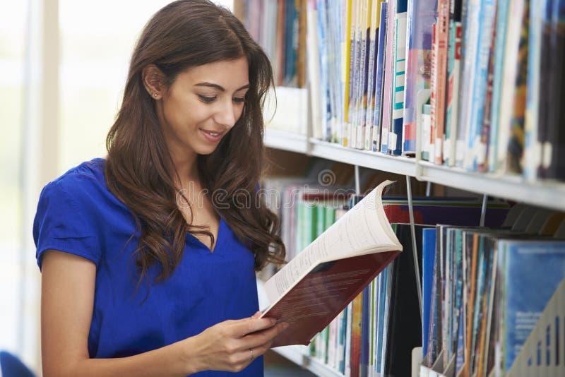 Étudiant féminin étudiant dans la bibliothèque photos libres de droits