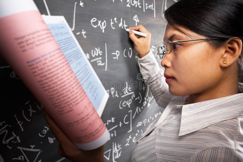 Étudiant féminin travaillant sur l'équation photos stock