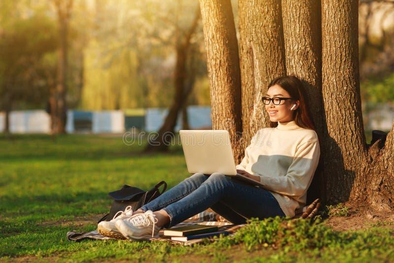 Étudiant Girl Using Laptop s'asseyant sous l'arbre au campus universitaire images libres de droits