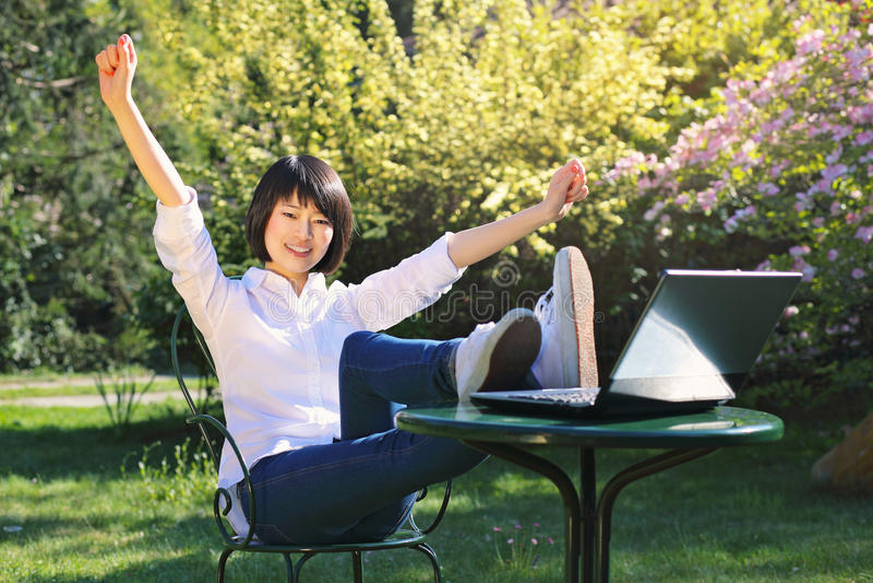 Étudiant heureux à l'aide de l'ordinateur portable dans le jardin photographie stock libre de droits