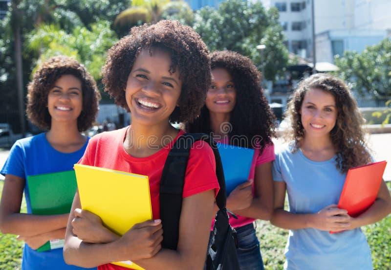 Étudiant heureux d'afro-américain avec le petit groupe de filles latines et caucasiennes images stock