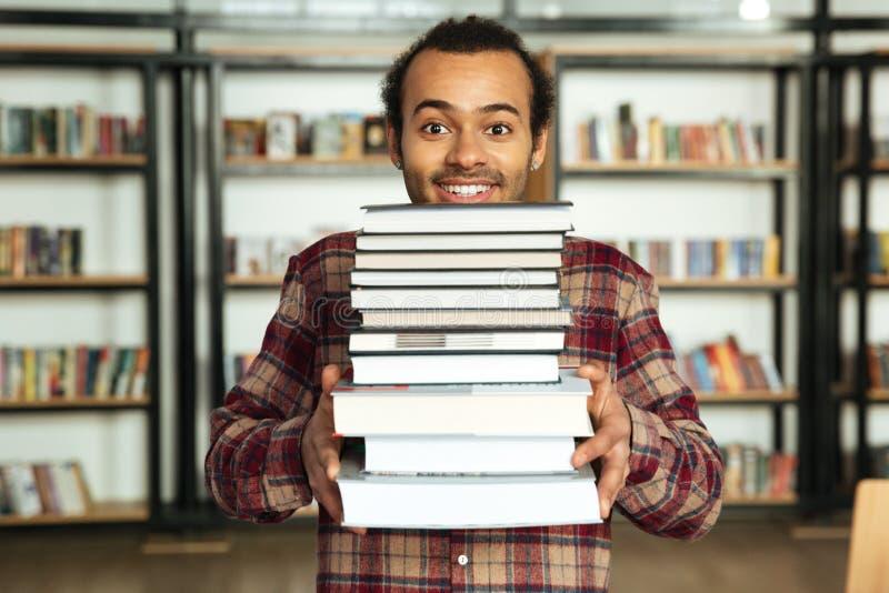 Étudiant heureux d'homme se tenant dans la bibliothèque avec le sort de livres image libre de droits