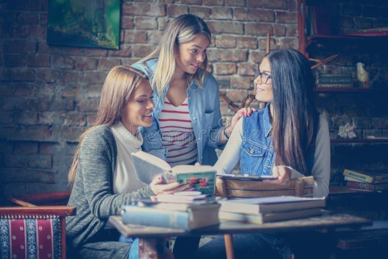 Étudiant heureux de trois grils apprenant ensemble à la maison images stock