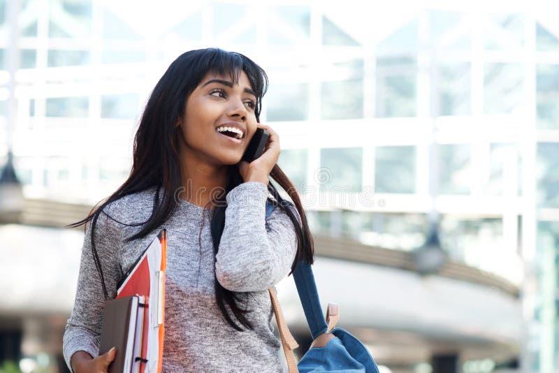 Étudiant indien heureux marchant et parlant avec le téléphone portable photographie stock