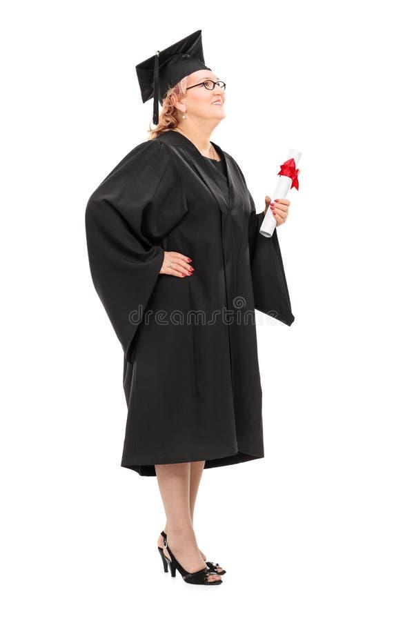 Étudiant mûr tenant un diplôme et recherchant photos libres de droits