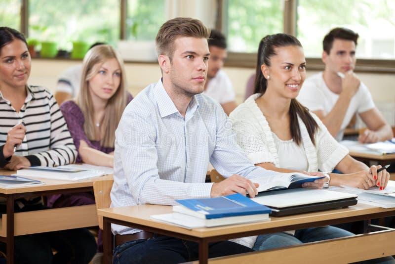 Étudiant masculin écoutant une conférence dans la salle de classe image stock