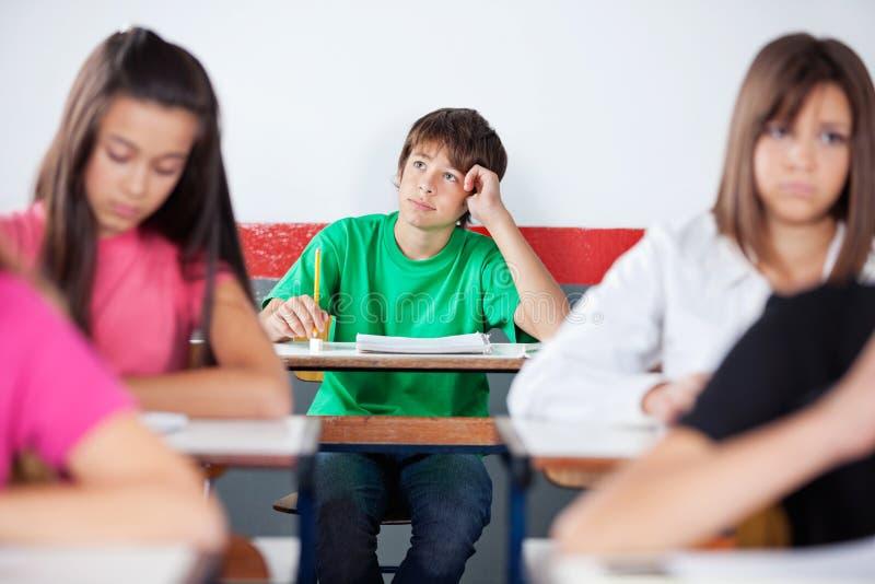 Étudiant masculin adolescent réfléchi Sitting At Desk photographie stock libre de droits