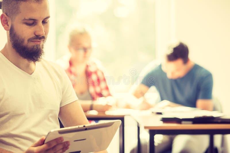 Étudiant masculin avec le comprimé devant ses camarades de classe photos stock