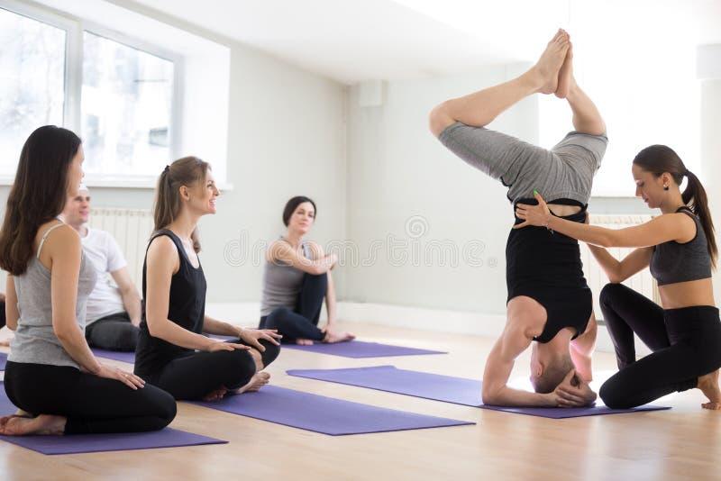 Étudiant masculin de aide de jeune instructeur féminin de yoga avec le headstand photos libres de droits