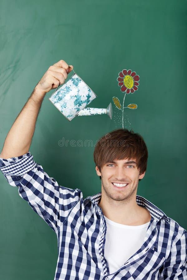 Étudiant masculin Holding Watering Can avec la fleur dessinée sur Chalkboar image stock