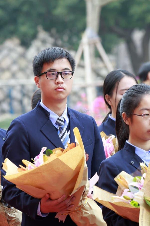 Étudiant masculin jugeant des fleurs prêtes à consacrer au professeur, adobe RVB photo stock