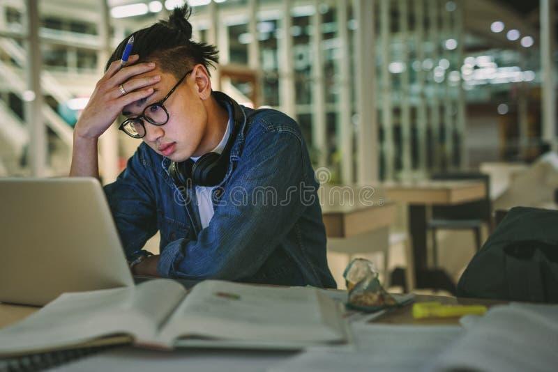 Étudiant masculin s'asseyant à la bibliothèque regardant l'ordinateur portable avec la main sur le front Étudiant déprimé s'assey image stock