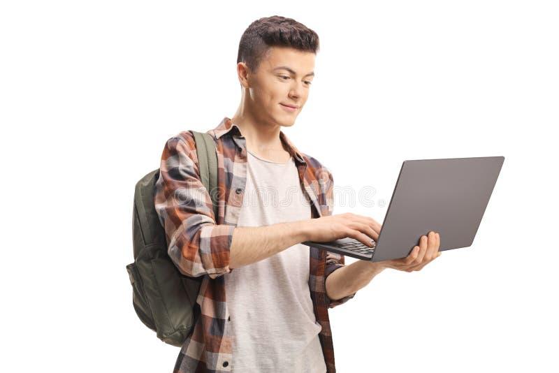 Étudiant masculin tenant un ordinateur portable et une dactylographie images libres de droits