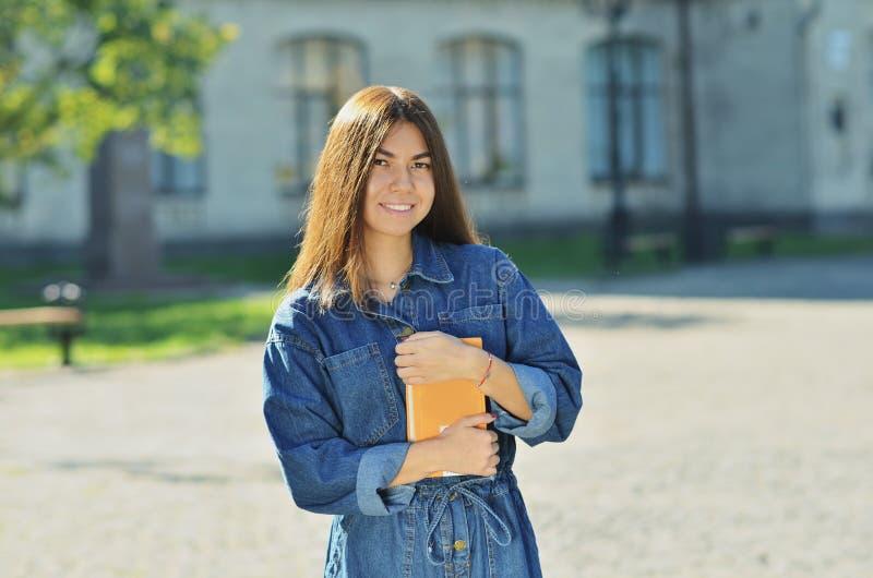 Étudiant mignon heureux de jeune femme tenant des livres et la marche photos libres de droits