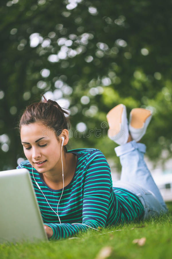 Étudiant occasionnel satisfait se trouvant sur l'herbe utilisant l'ordinateur portable photos libres de droits