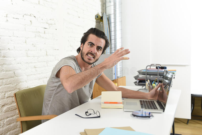 Étudiant ou homme d'affaires moderne de style de hippie travaillant dans l'effort avec le renversement fâché de bureau d'ordinate photo stock