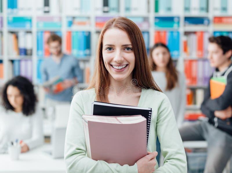 Étudiant posant avec des carnets images libres de droits