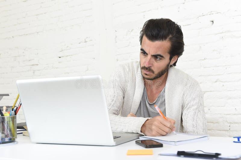 Étudiant préparant le projet d'université ou homme d'affaires d'indépendant de style de hippie travaillant avec l'ordinateur port photo stock