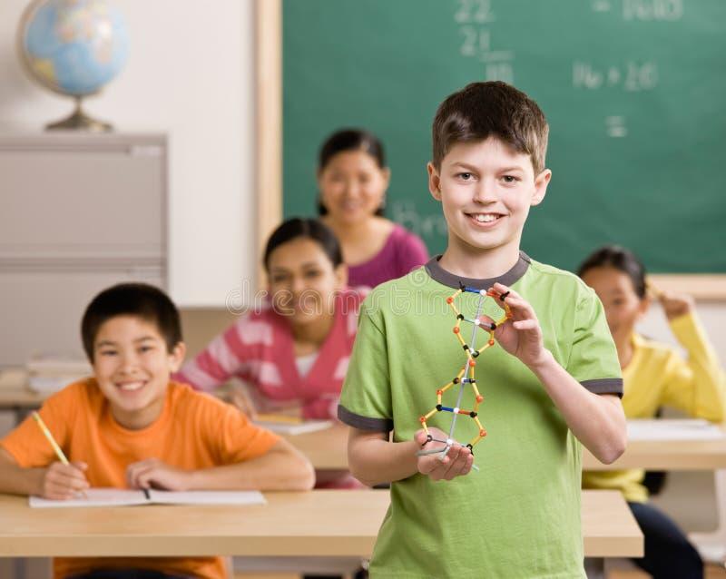 Étudiant retenant le modèle moléculaire dans la salle de classe photos libres de droits
