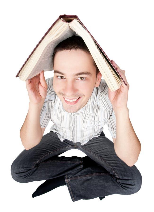 Étudiant retenant un livre au-dessus de sa tête photo libre de droits