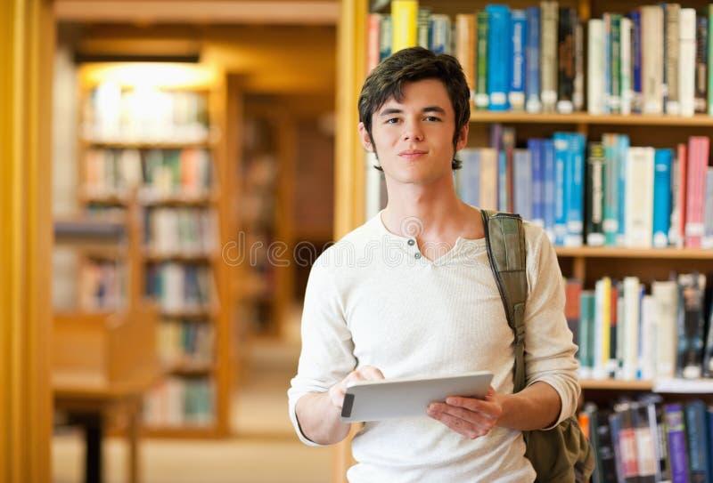Étudiant sérieux retenant un ordinateur de tablette photographie stock