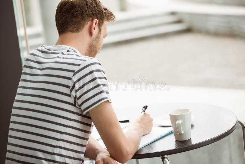 Étudiant s'asseyant avec une boisson chaude et écrivant sur le bloc-notes photographie stock