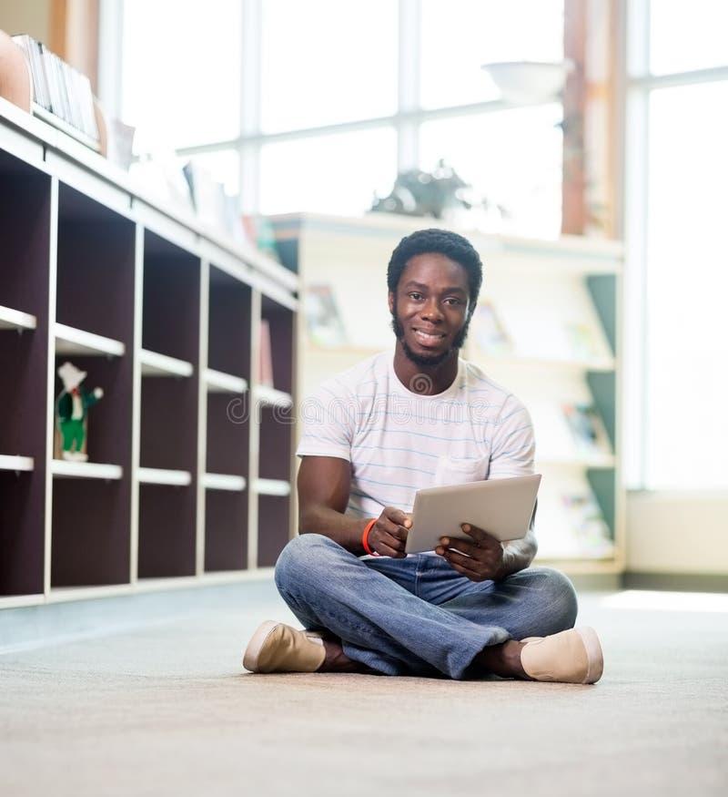 Étudiant sûr With Digital Tablet dans la bibliothèque images libres de droits