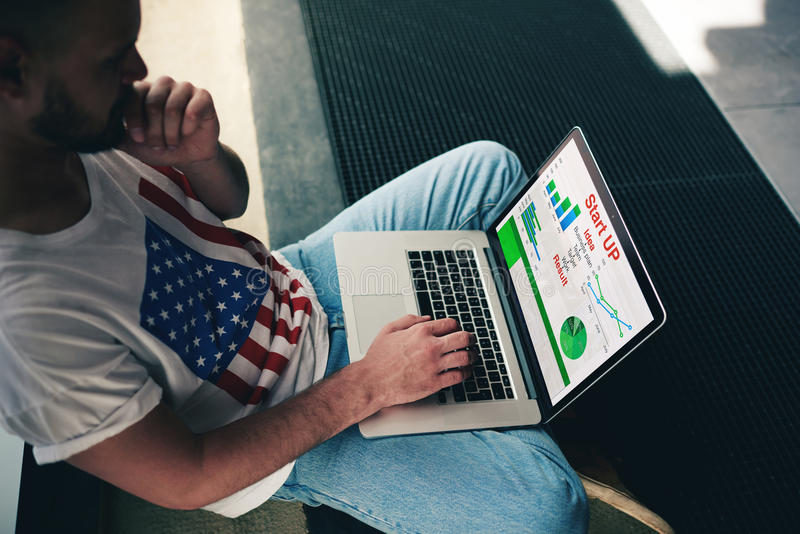 Étudiant se renseignant sur des statistiques des plus-values utilisant son ordinateur portable photos stock