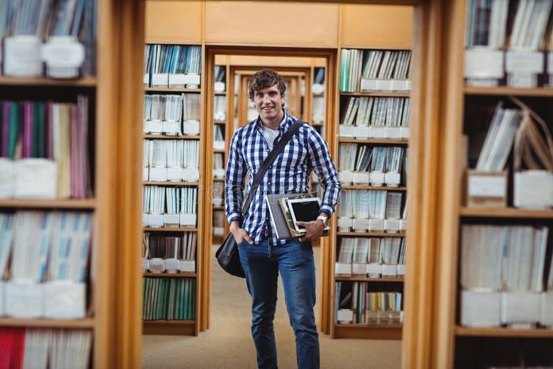 Étudiant se tenant dans la bibliothèque avec l'ordinateur portable et le comprimé numérique photographie stock