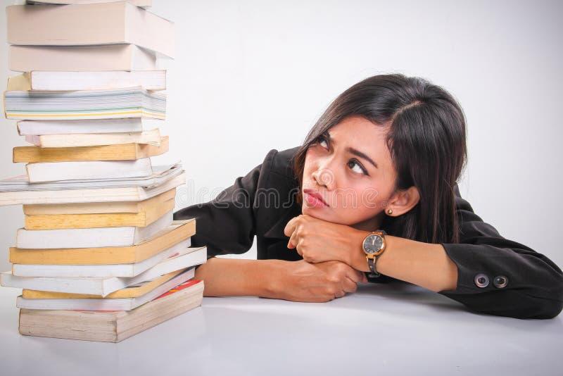 Étudiant sous pression, se penchant vers le bas tout en regardant la pile des livres images stock