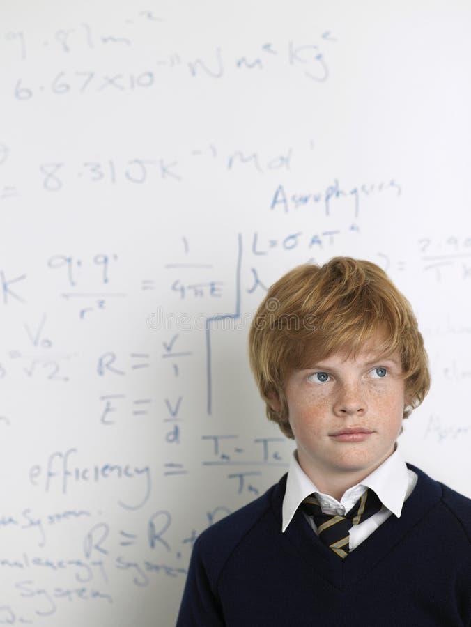 Étudiant Standing By Whiteboard dans la classe de maths photo libre de droits