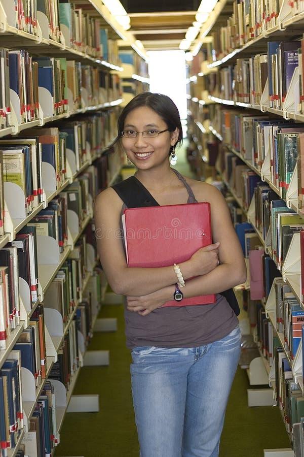 Étudiant universitaire à une bibliothèque photo stock