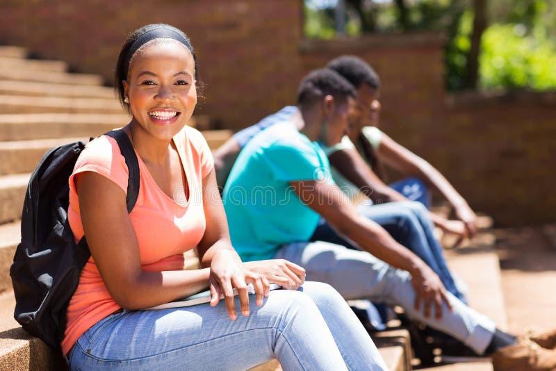 Étudiant universitaire afro-américain féminin s'asseyant sur des étapes image stock