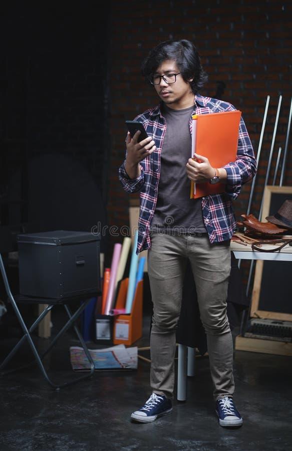 Étudiant universitaire asiatique Checking Phone et livres de se tenir à l'intérieur de Wa photos libres de droits