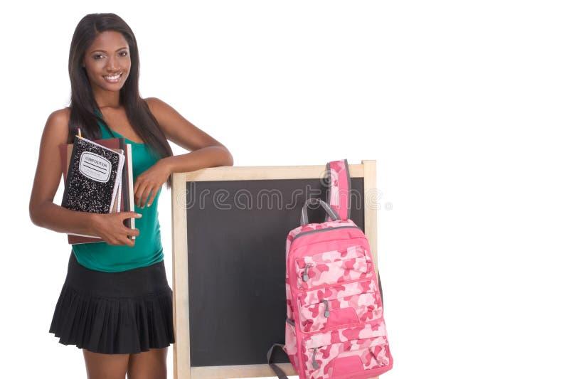 Étudiant universitaire d'Afro-américain par le tableau noir photo stock