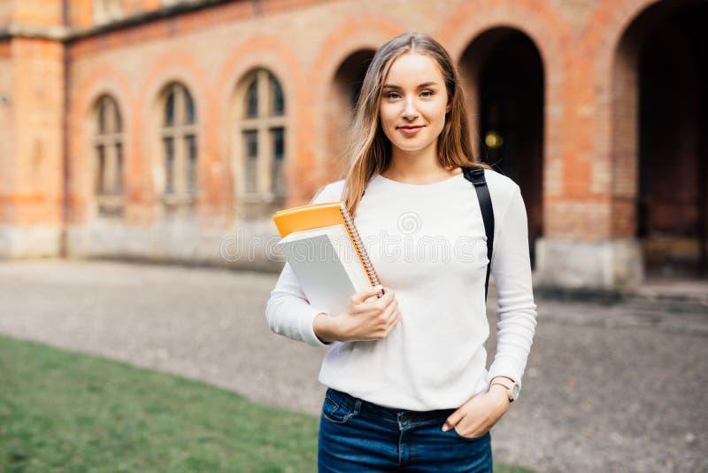 Étudiant universitaire féminin futé avec le sac et livres sur le campus dehors image libre de droits