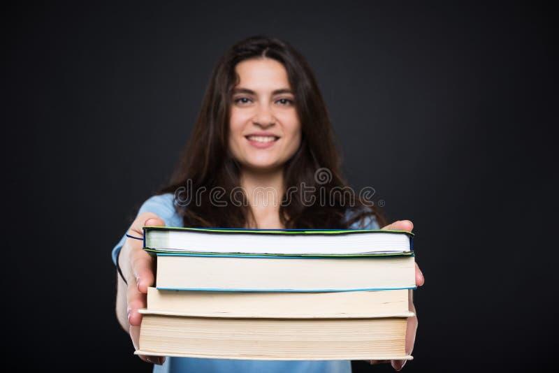 Étudiant universitaire heureux tenant des manuels et le sourire photographie stock