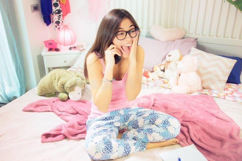 Étudiant universitaire hispanique mignon criant pour le bonheur au téléphone se reposant dans le lit image stock