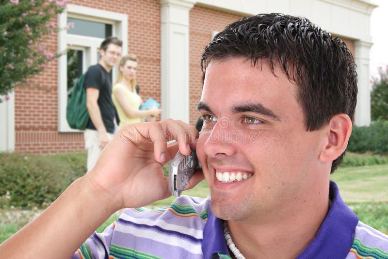 Étudiant universitaire parlant sur le téléphone portable sur l'université C image stock