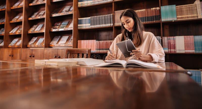 Étudiant universitaire prenant des notes d'ouvrage de référence photo libre de droits