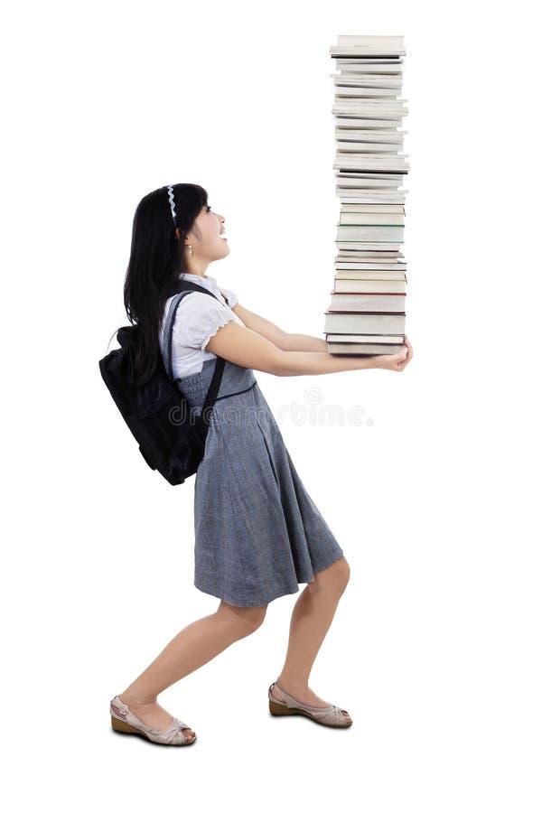 Étudiant universitaire tenant la pile des livres photos stock