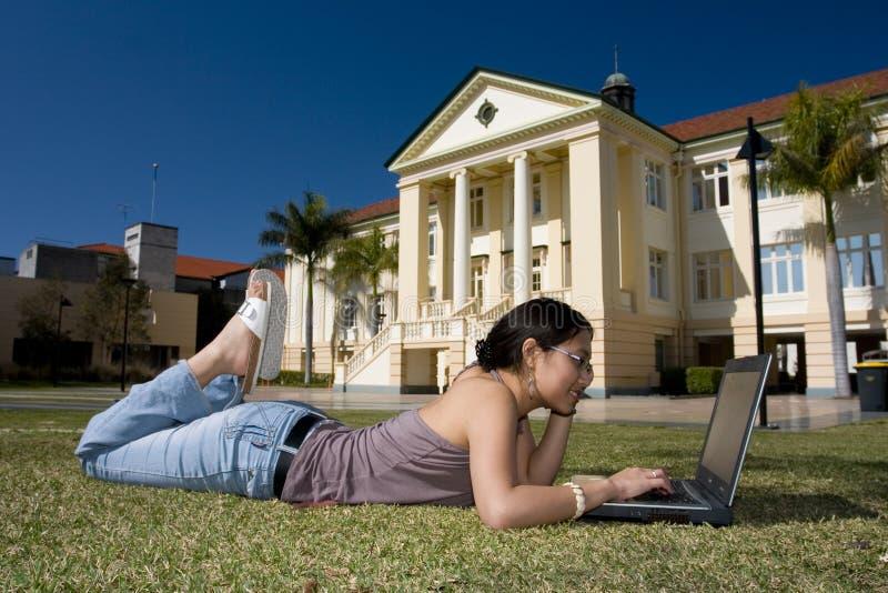Étudiant universitaire travaillant avec l'ordinateur portatif photographie stock libre de droits