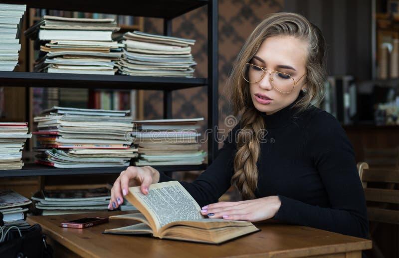 Étudiante à la bibliothèque, elle s'assied au bureau et au concept d'amélioration d'étude, d'éducation et d'individu photo libre de droits