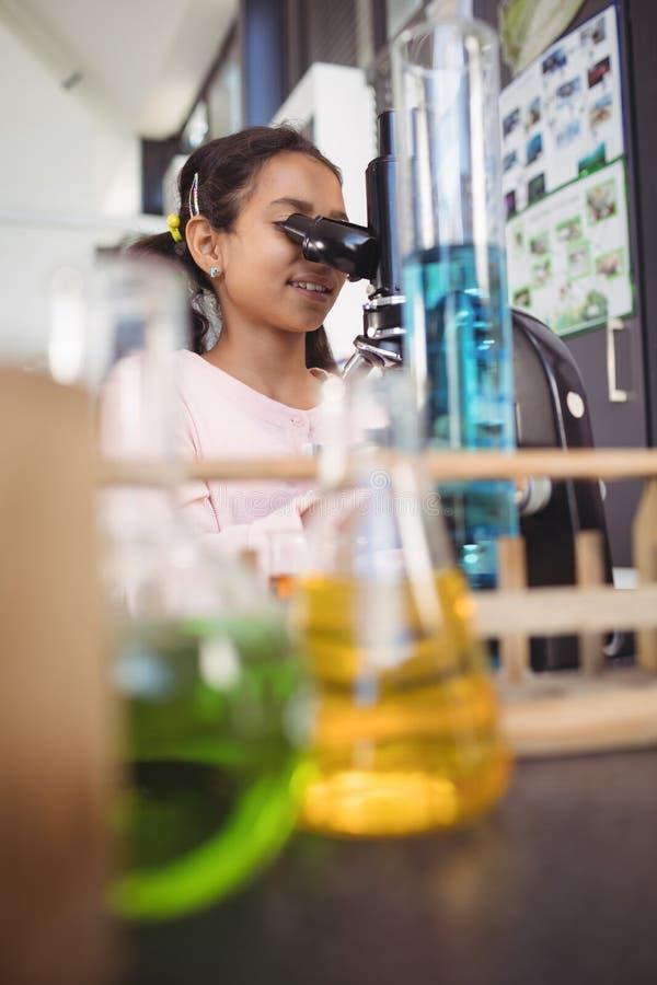 Étudiante élémentaire à l'aide du microscope au laboratoire images stock